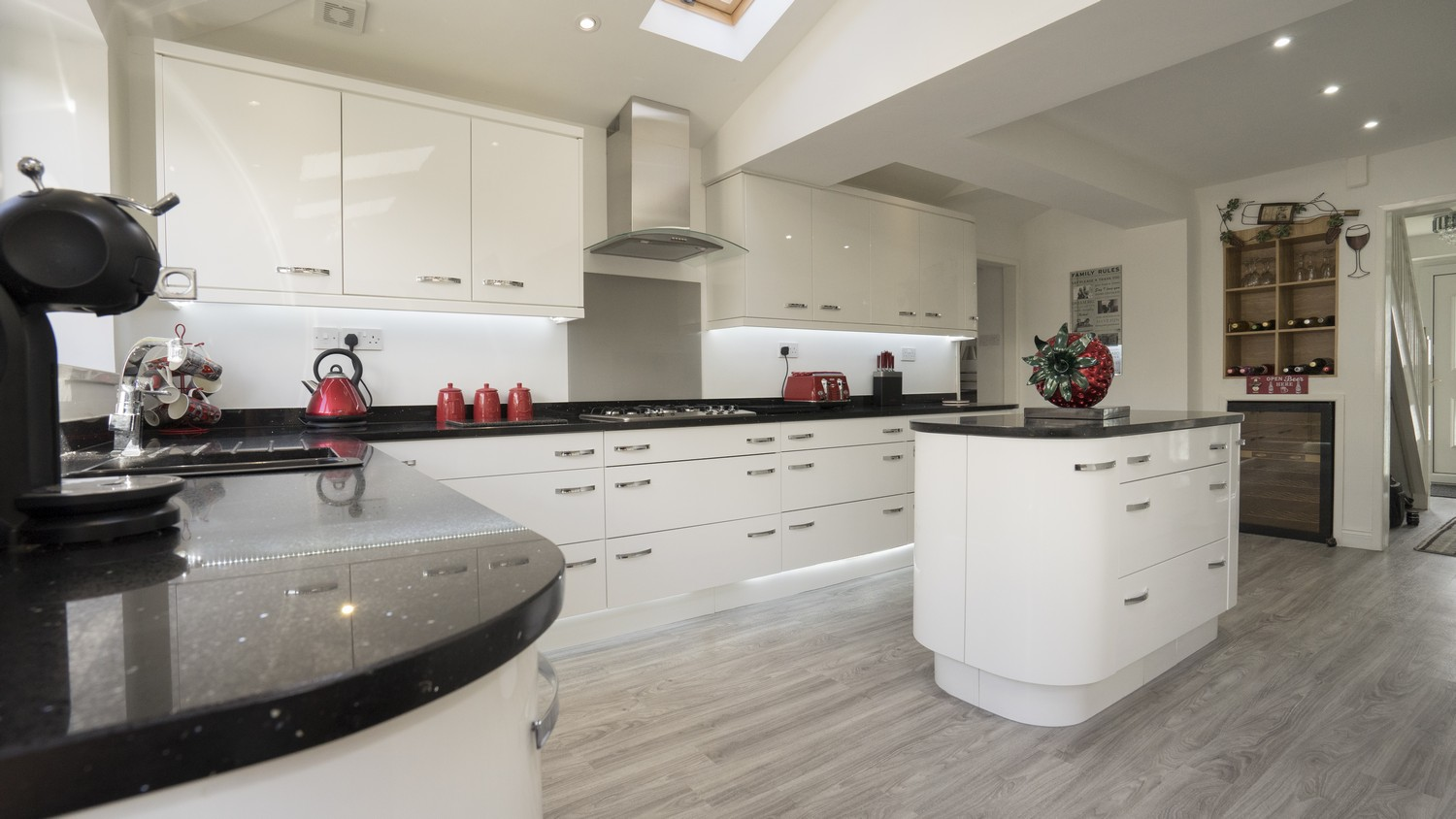Gloss white kitchen with central island with curved corner cupboards and a large selection of drawers.