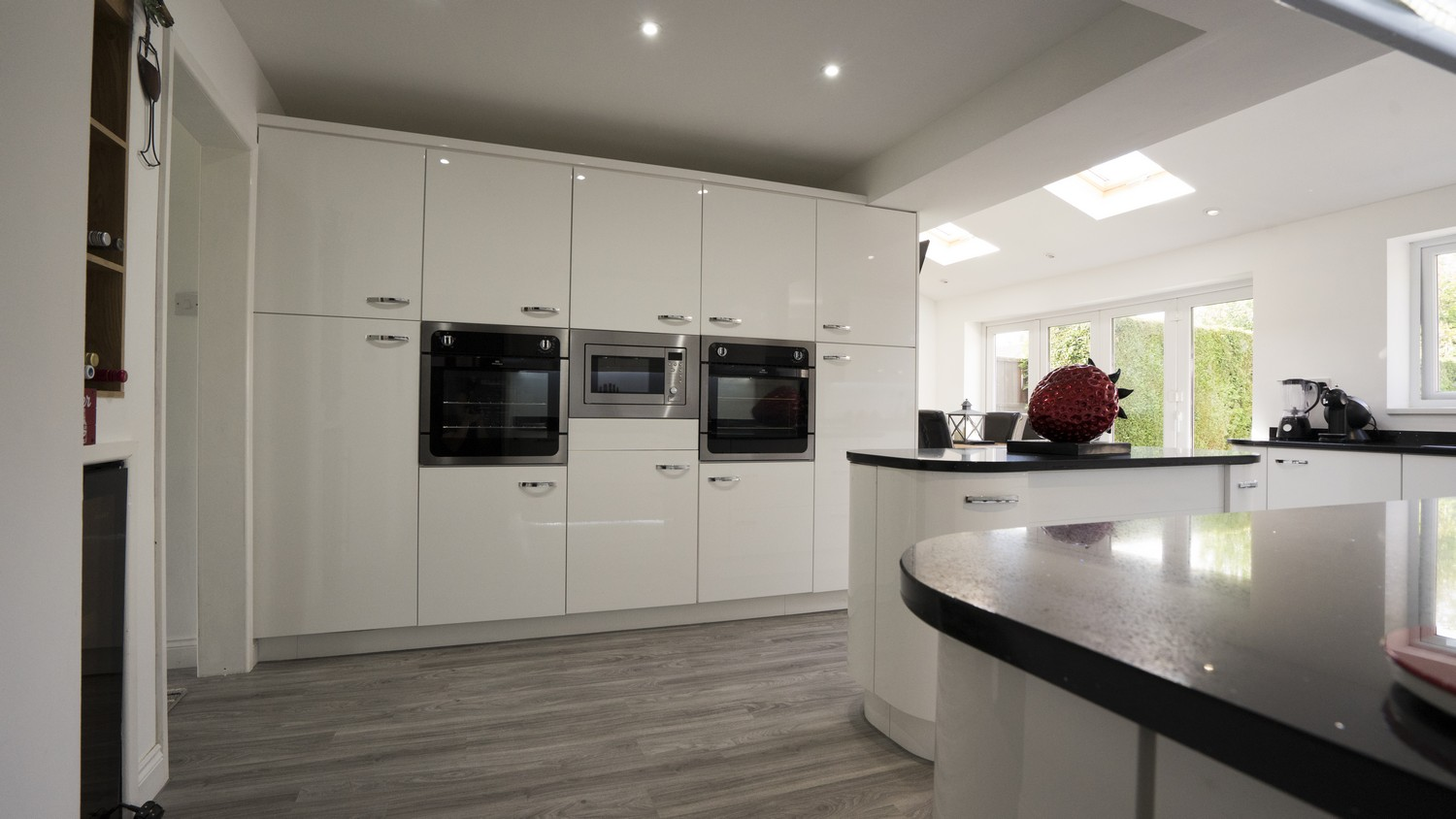 Close up of the floor to ceiling cupboards with integrated appliances, notice the bi-folding doors in the background leading onto the garden.