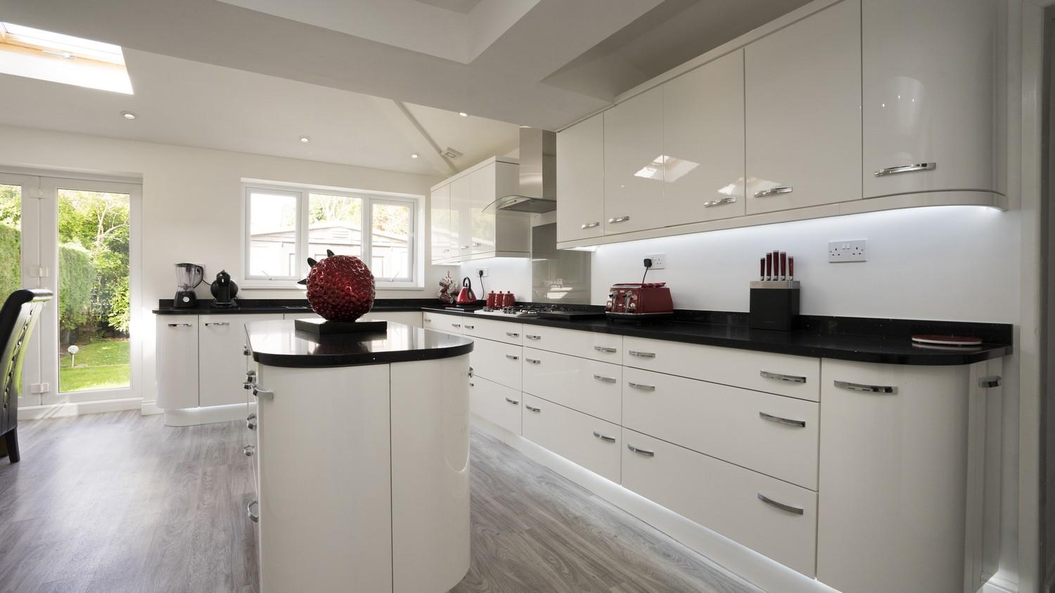 Gloss white kitchen with chrome handles featuring various draw units and rounded corner cupboards.