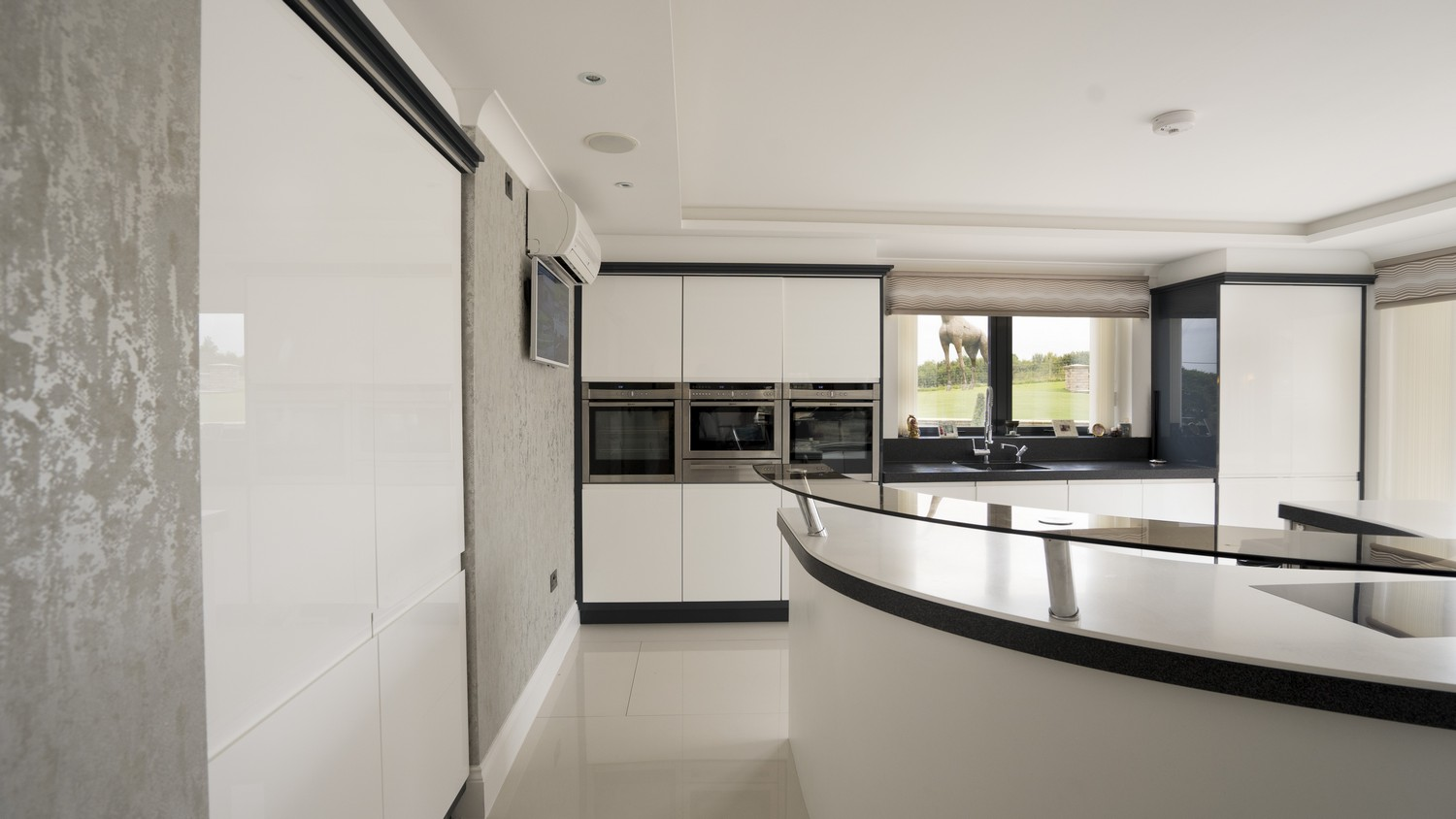 Straight on view of the gloss white Corian designer kitchen, notice the large doors sunk within the left wall housing the integrated fridge/freezer.