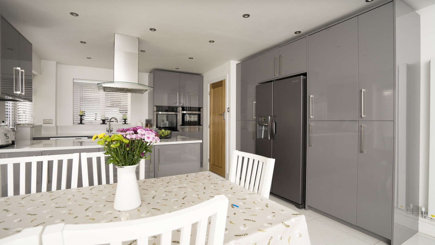 Grey gloss kitchen with integrated appliances and large fridge/freezer in Kirkby, Liverpool. The kitchen features a ceiling hung extractor fan and floor to ceiling cupboards.