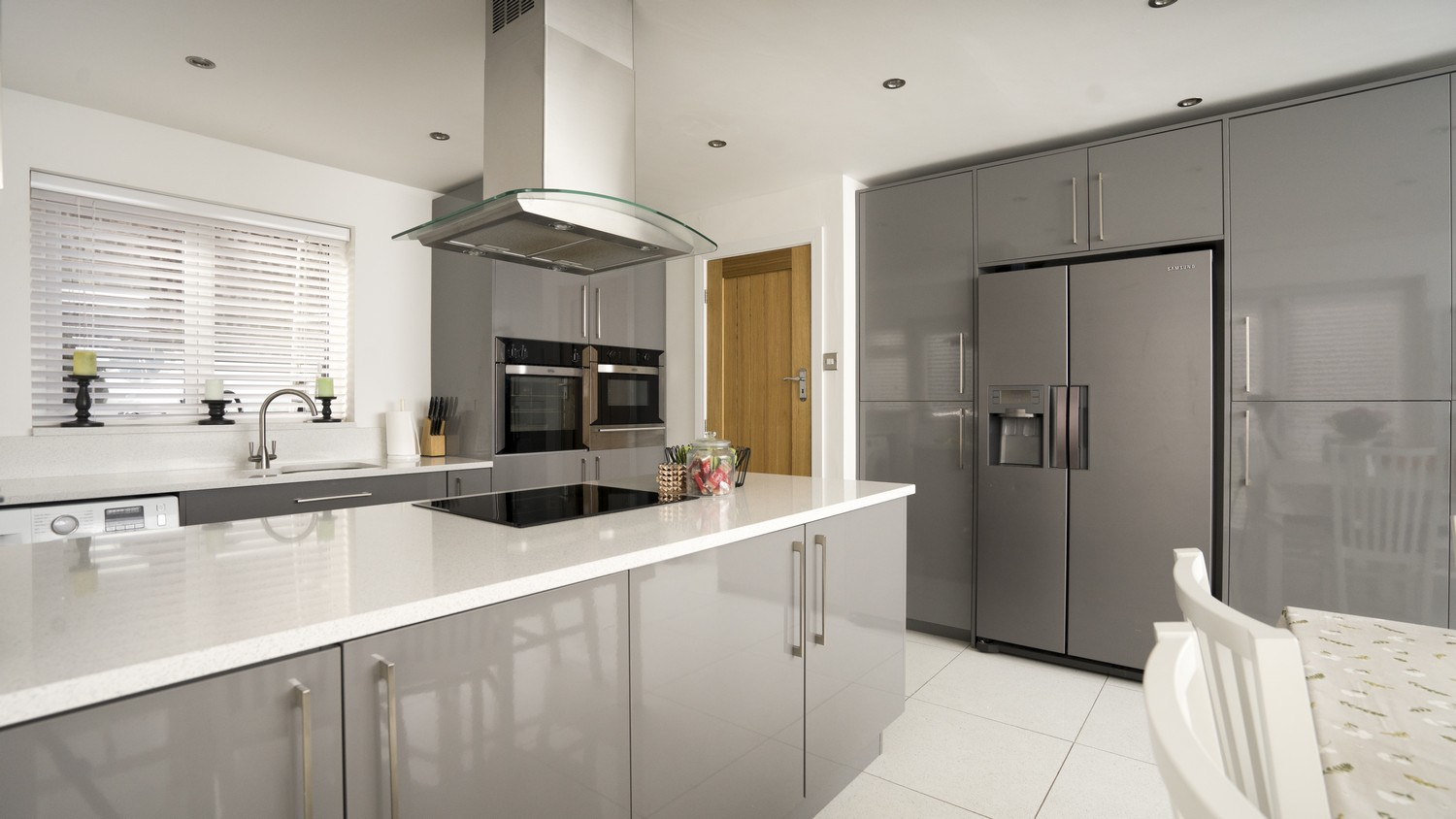 Grey Gloss kitchen with large stainless steel handles, matching kick-boards and end-panels.