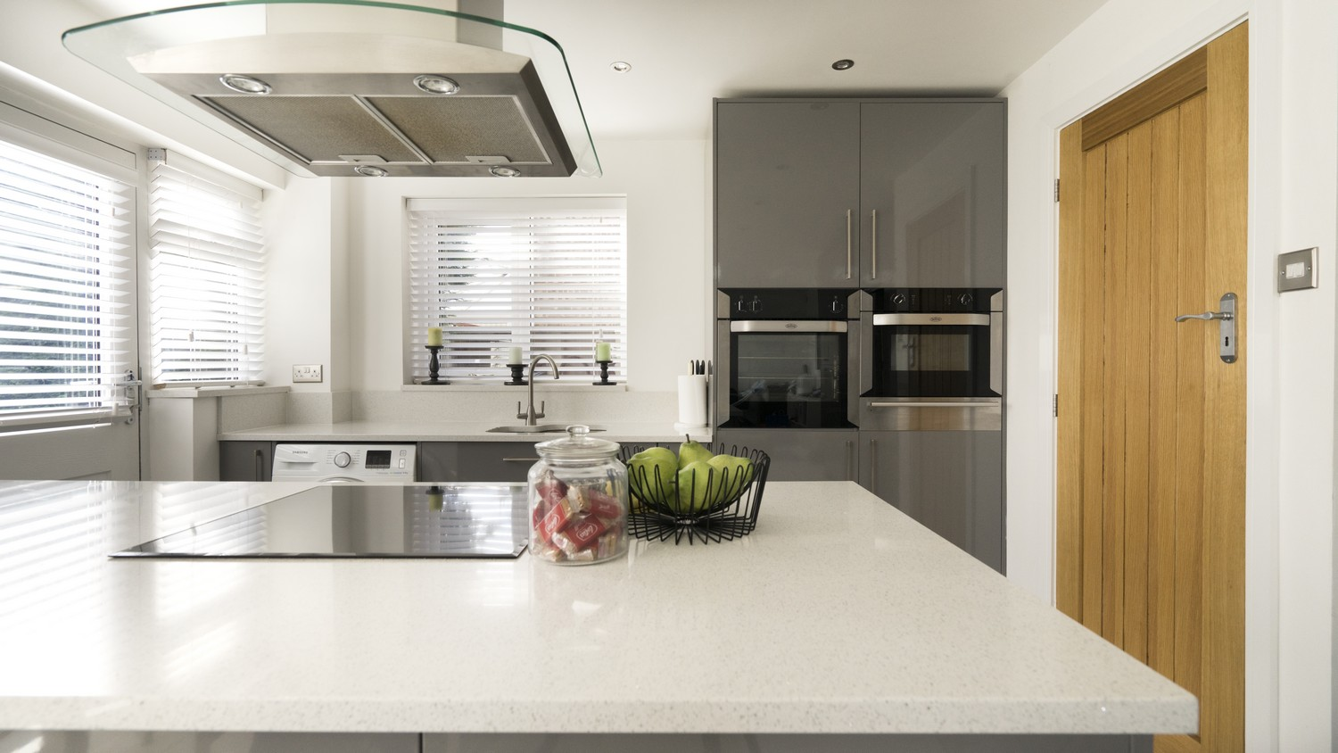 Straight on view of the grey gloss kitchen in Kirkby, Liverpool featuring white glitter Corian worktops, integrated appliances and integrated cooking hob.