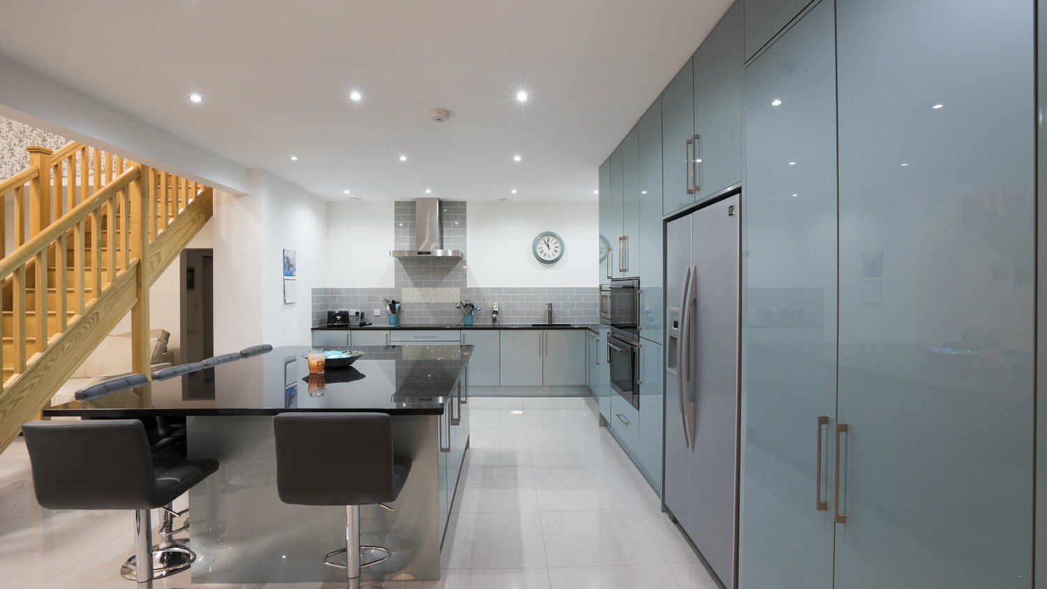 Alternative view of this stunning blue gloss kitchen with floor to ceiling cupboards and large American style fridge/freezer.