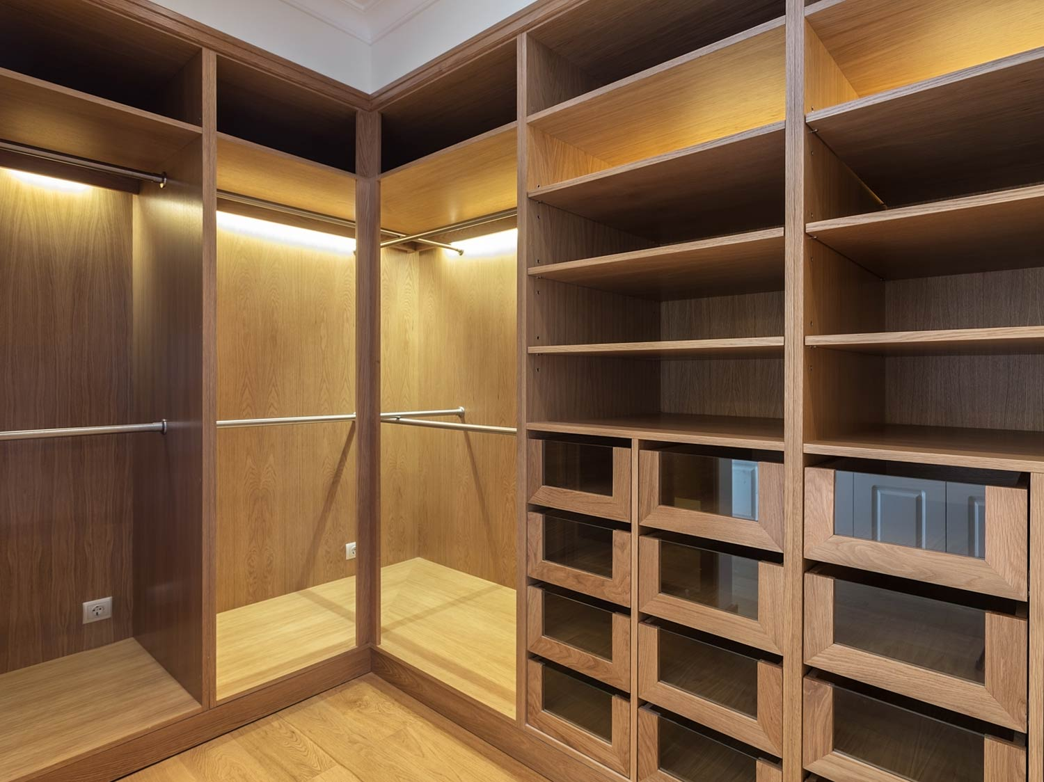 Oak style walk in wardrobe with chrome hanging poles, adjustable shelving and glass fronted draws. This walk in wardrobe was designed for a client in Liverpool and is a great example of the type of work we can do.