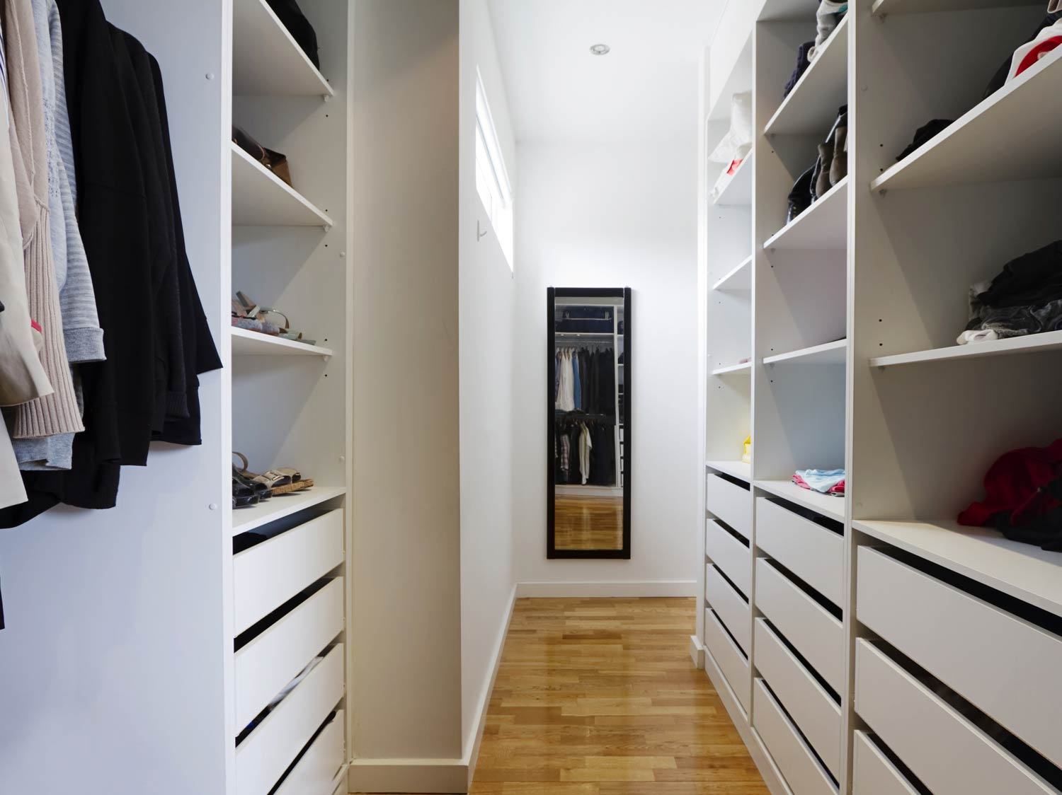 Simplistic white walk in wardrobe solution with adjustable storage shelving and pull out handl-less draws. This solution gives plenty of choice for storing all types of clothing, shoes and accessories.
