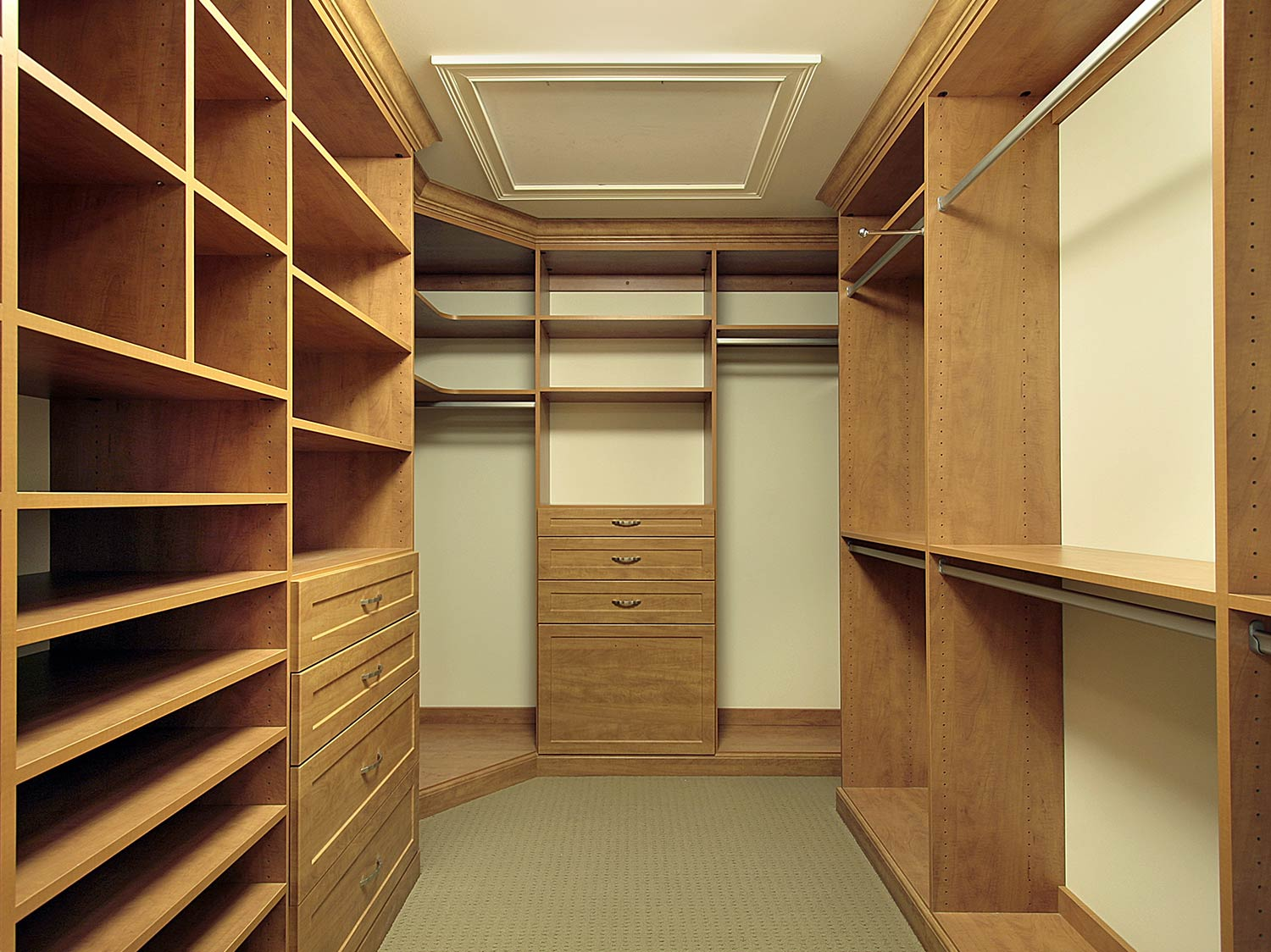 Oak traditional style walk in wardrobe with various shelving units, hangers and draws.