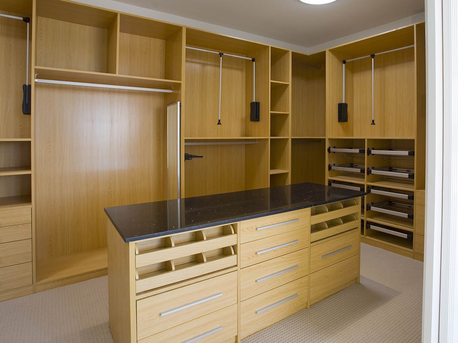 Contemporary oak walk in wardrobe with granite effect tops. Various storage solutions have been used here including pull out hangers for easy access, pull out shelves, draws and pull out tie racks.