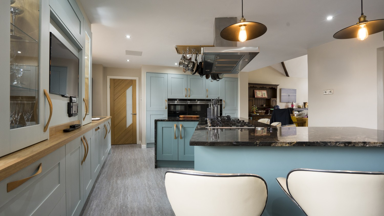 Blue shaker kitchen featuring a large central cooking hob with extractor fan, a perfect setup for any keen chef.