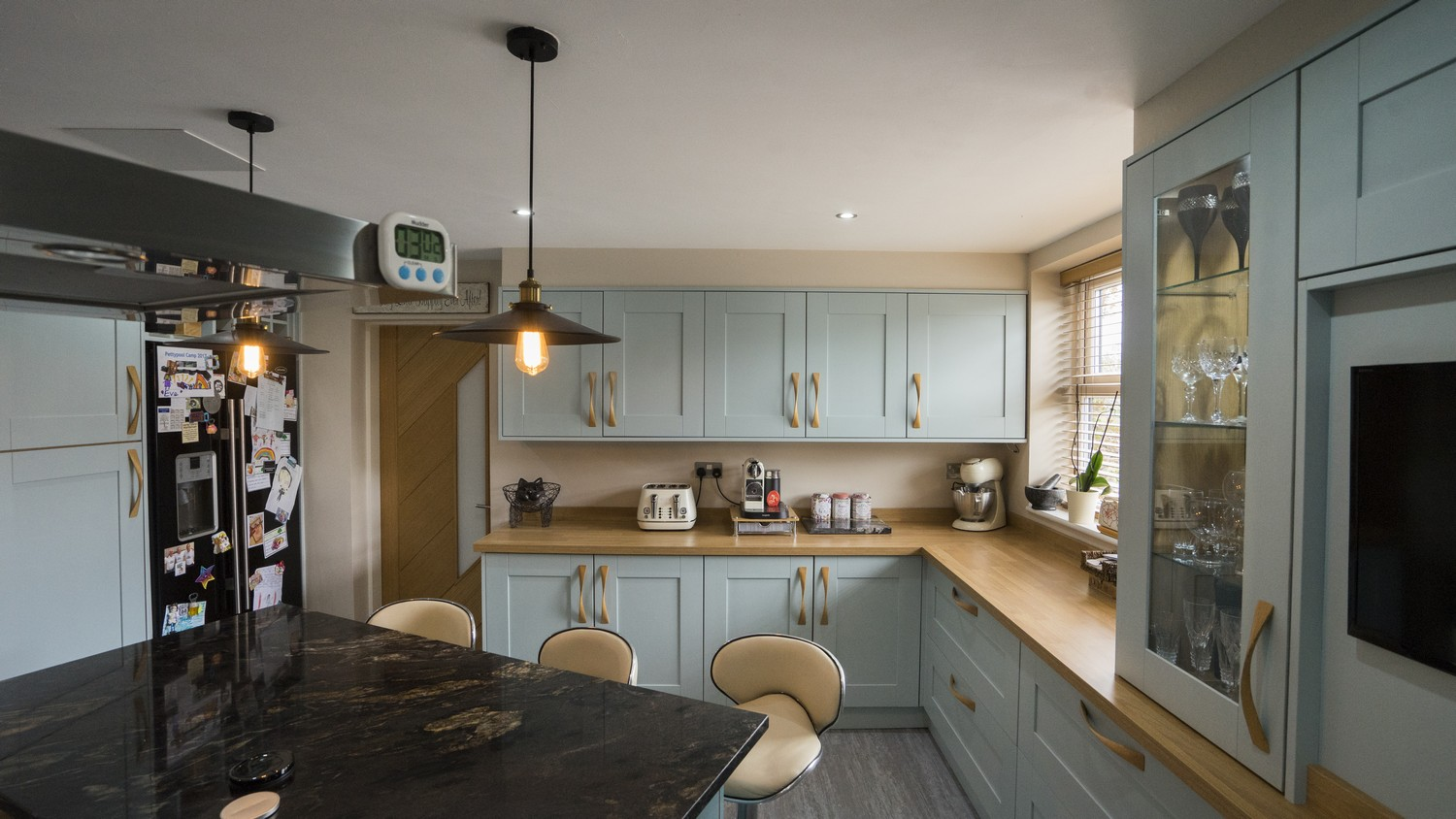 This family kitchen has oak timber worktops around the outer cupboards with matching bespoke oak handles throughout.