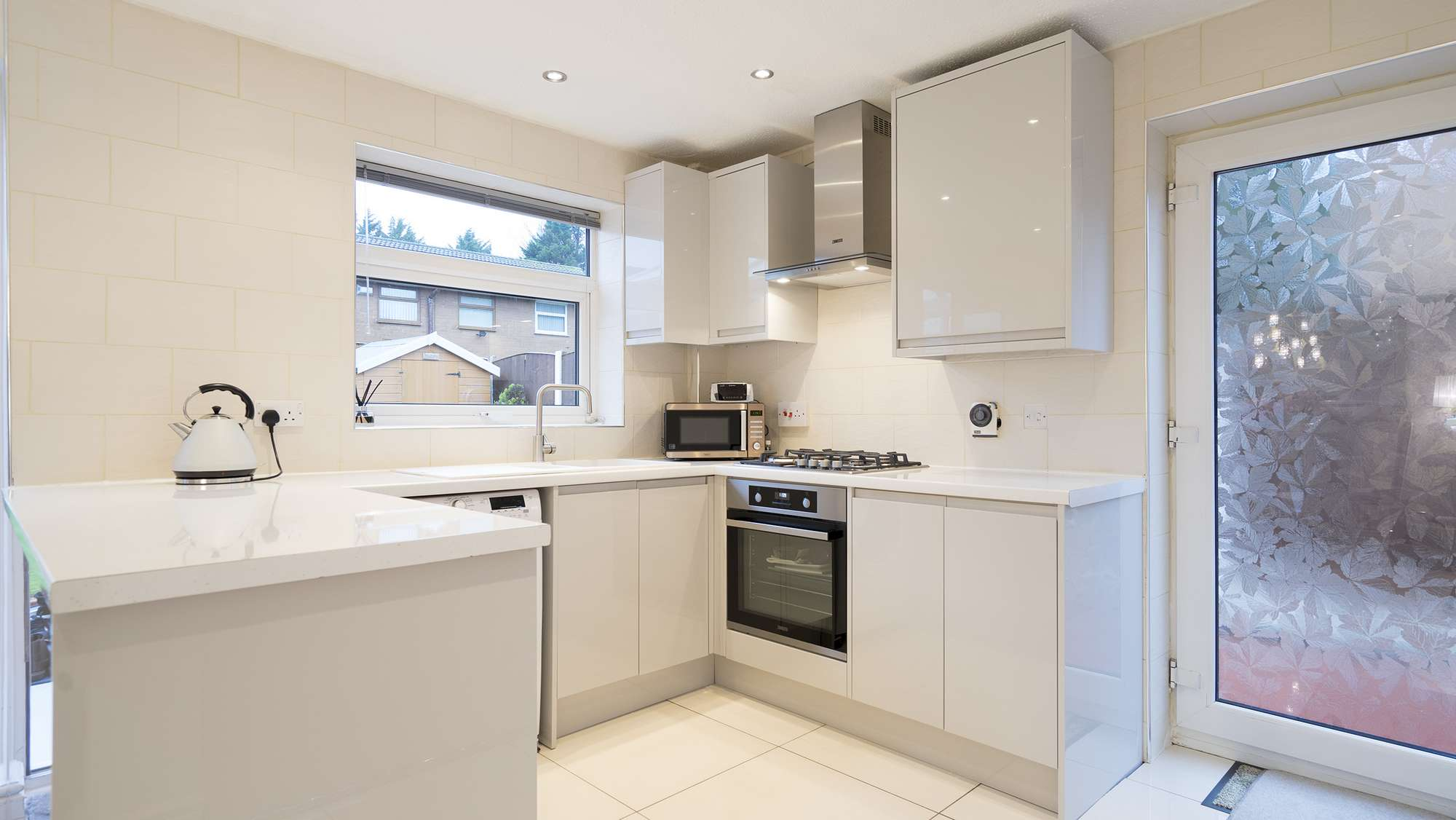 Another angle of the handleless kitchen featuring lots of storage space and low maintenance finishes.