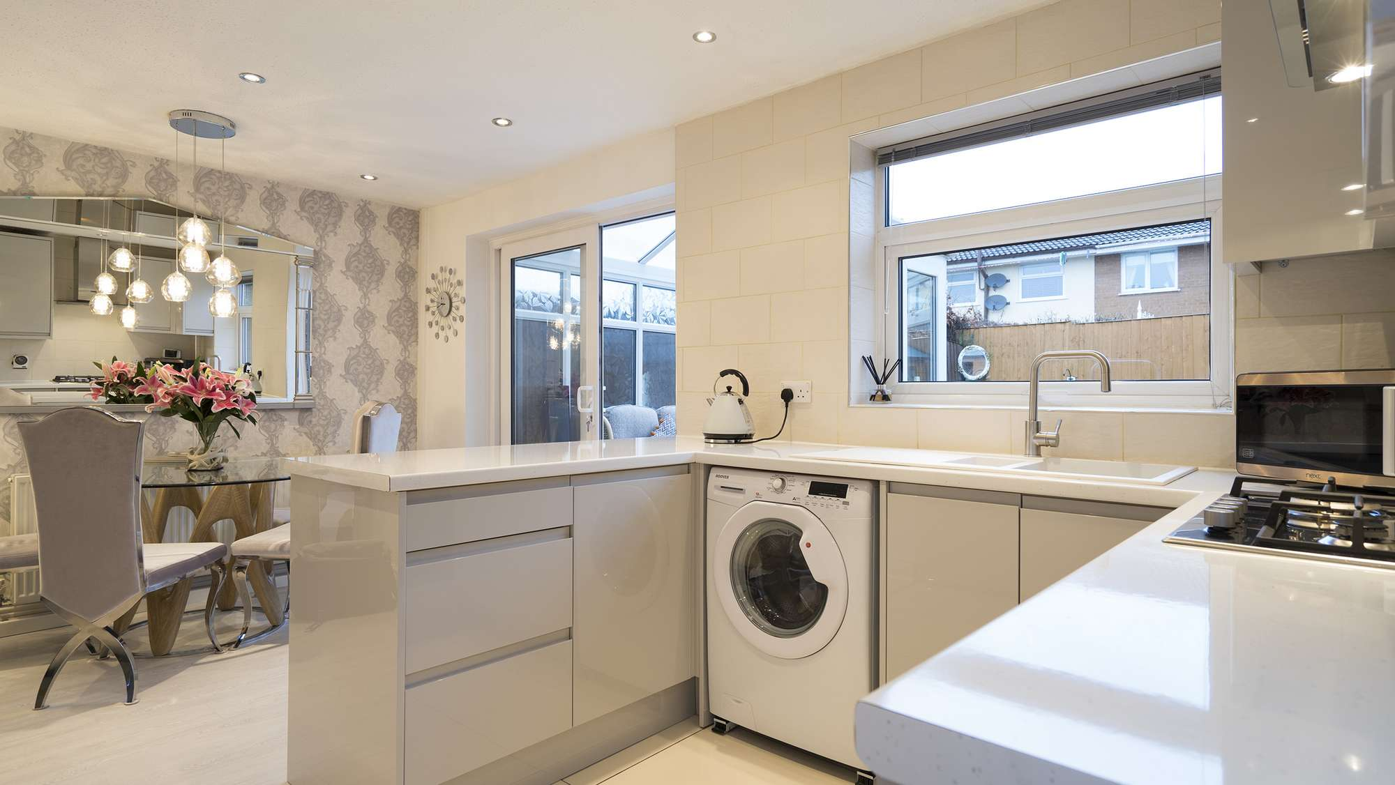 Light grey gloss C shape handle-less kitchen with white sparkle worktops and stainless steel hardware.