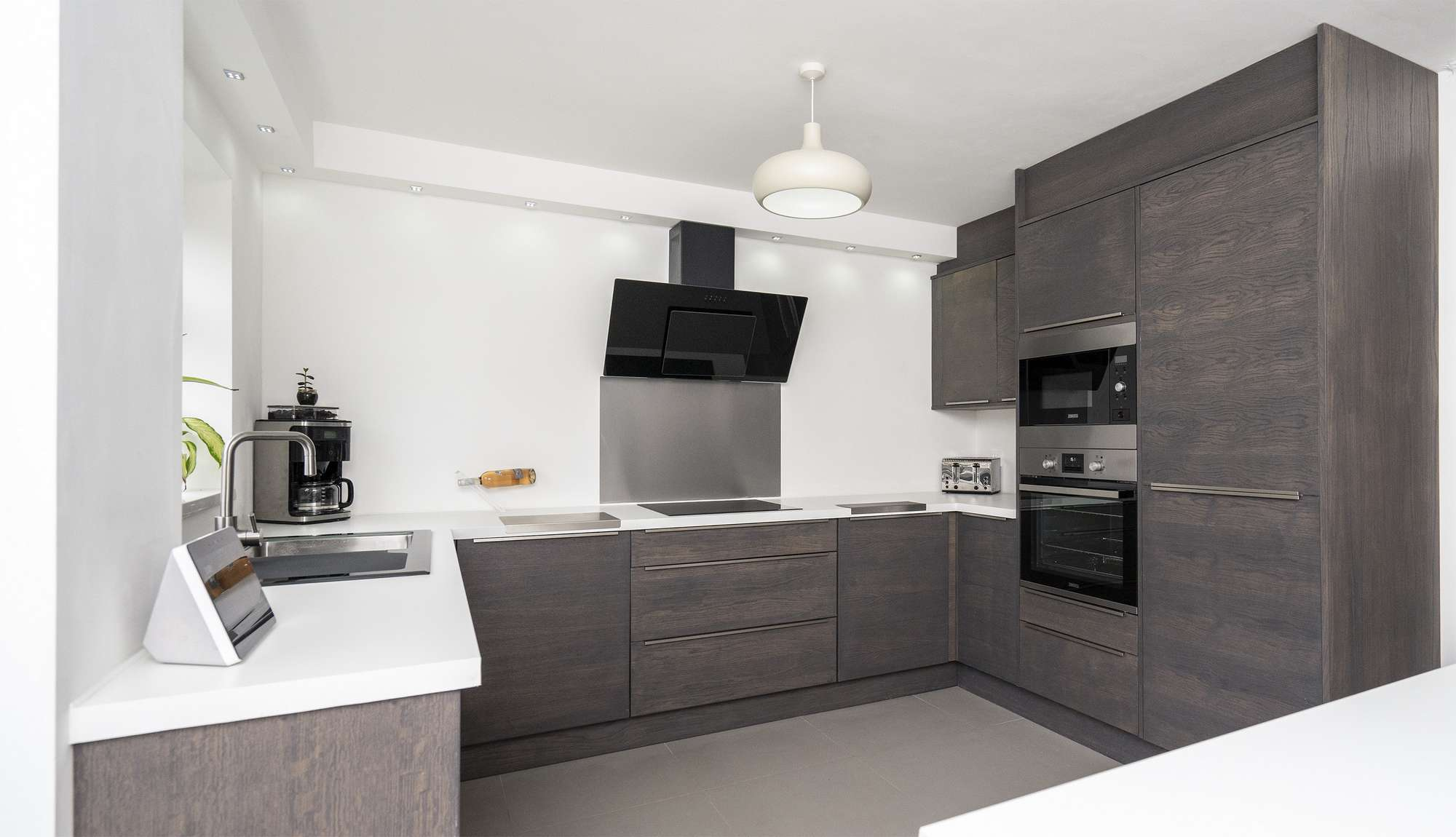 Walnut slab kitchen with slimline stainless steel handles and integrated appliances.