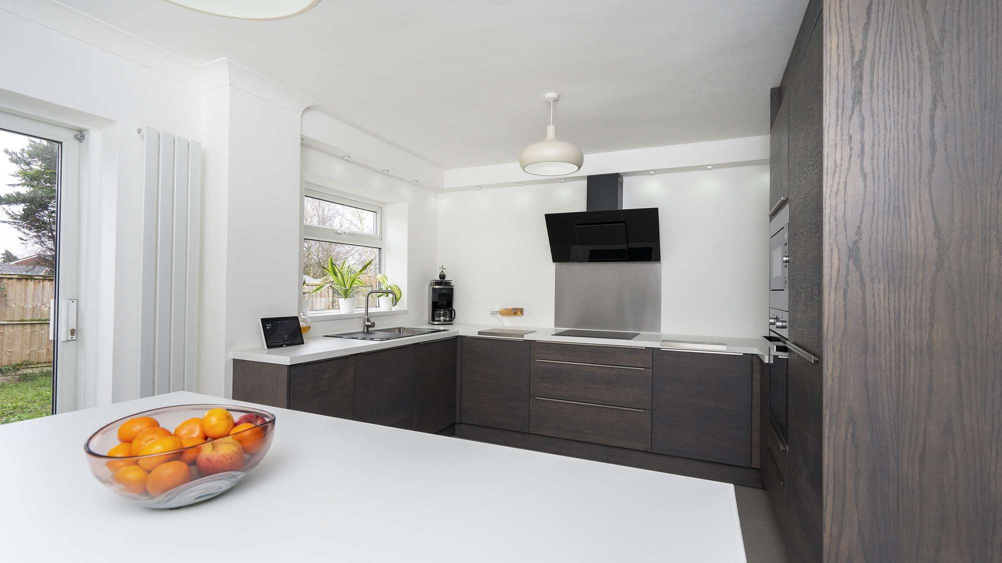 Alternative view of this modern walnut slab kitchen with white worktops and stainless steel accents.