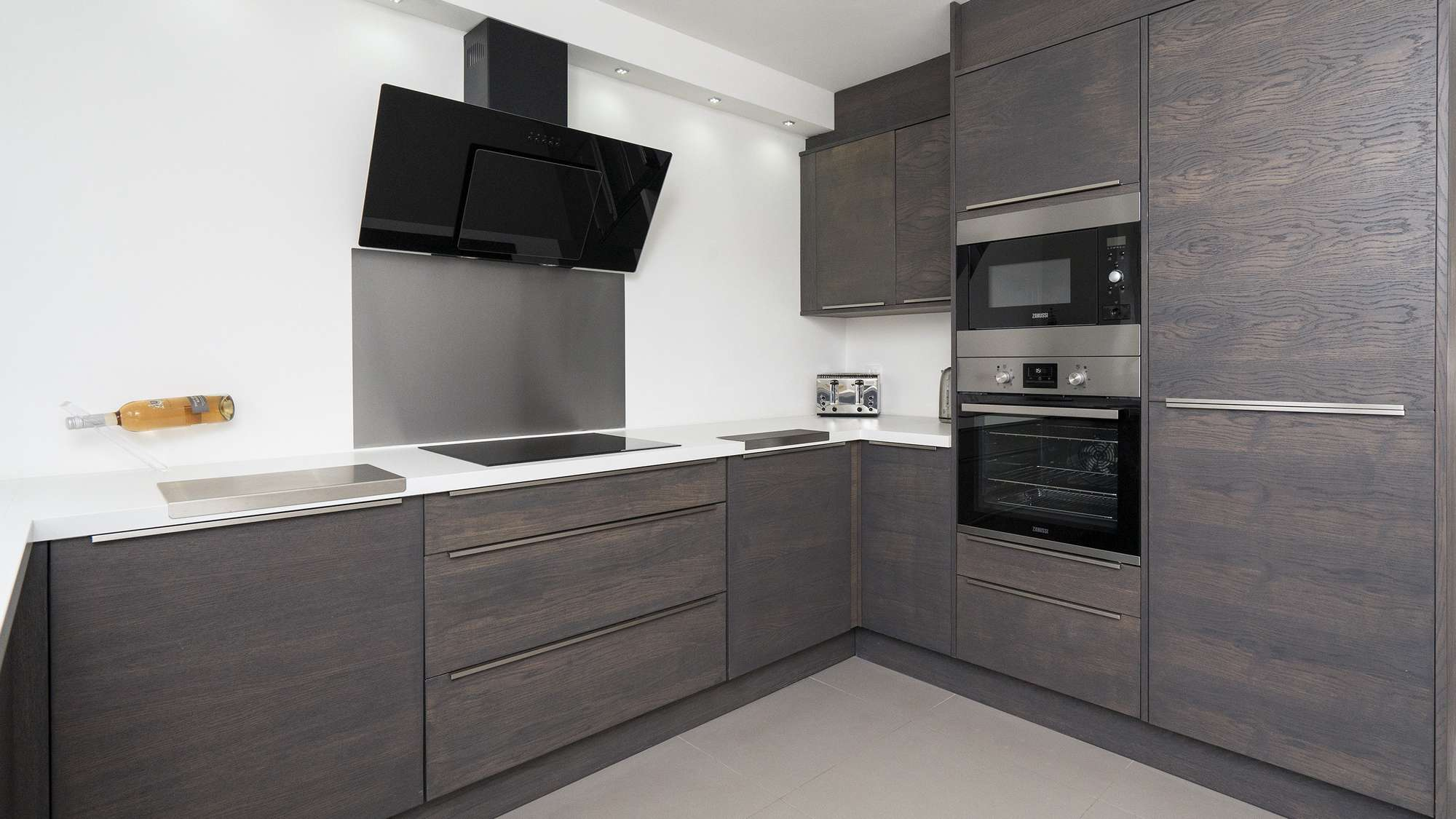 Close up of the cooking area with built in oven, microwave and ceramic hob. Large black extractor above the hob.