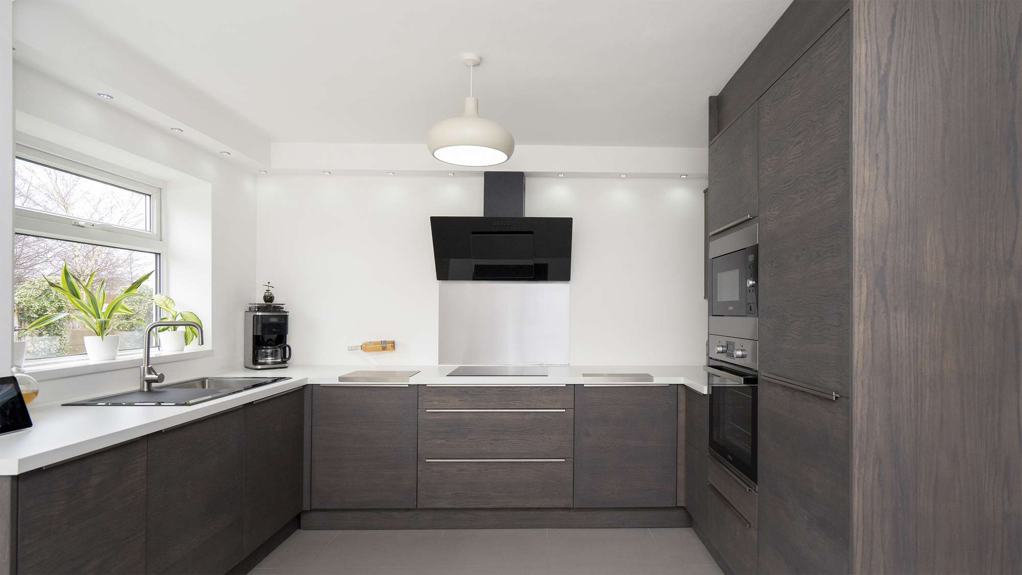 Straight on shot of the walnut slab kitchen with contrasting white worktops.