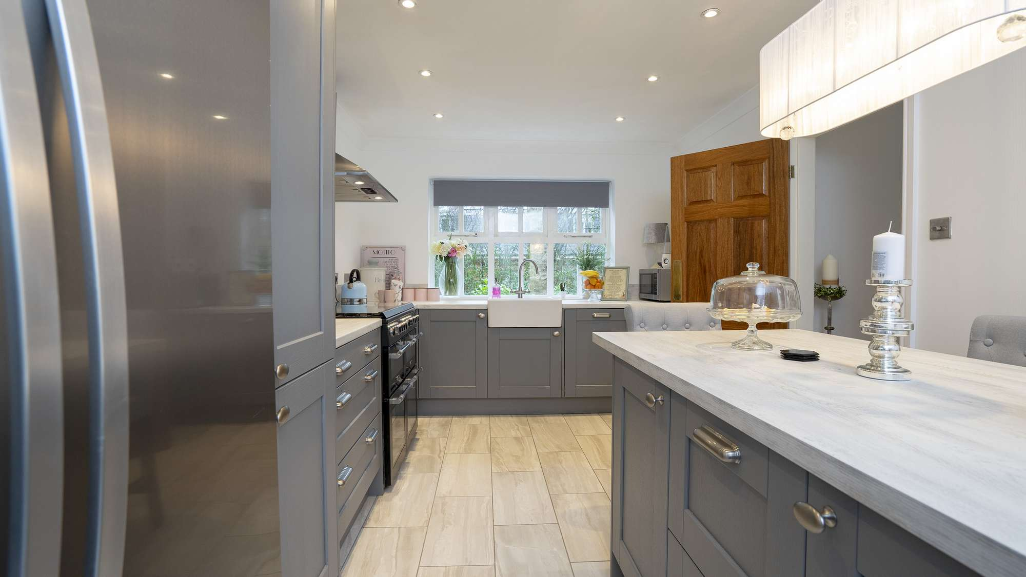 Straight on view of the grey shaker kitchen with white faux wood worktops.