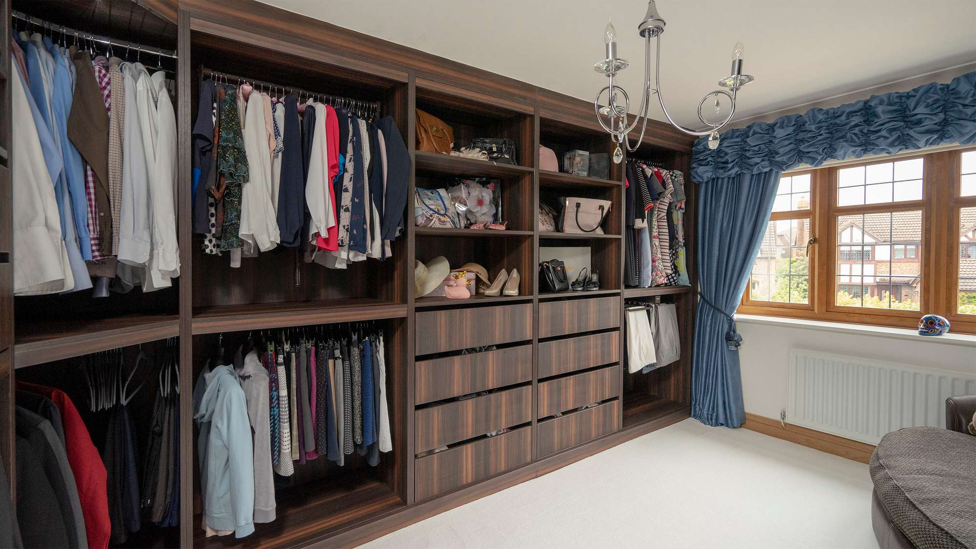 Image showing some of the storage on offer in this stunning walk-in wardrobe featuring clothing rails, central shelving and drawers.